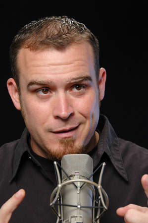 comedian: Broadcaster on the microphone on a black background
