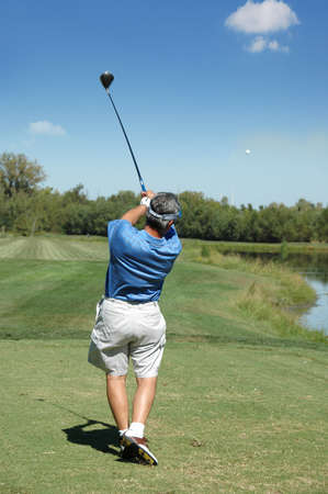 follow through: Golfer tees of on a beautiful sunny day