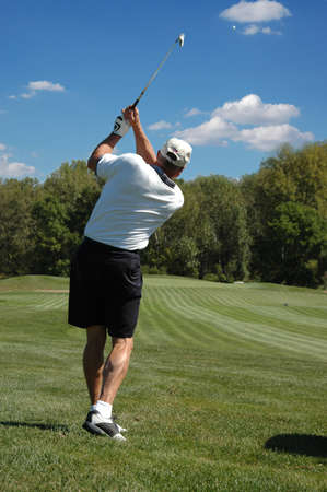 follow through: Golfer in the after swing looking on a beautiful sunny day