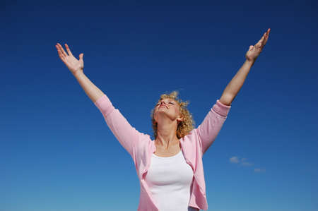 rejoice: Woman with her arms wide open against a blue sky
