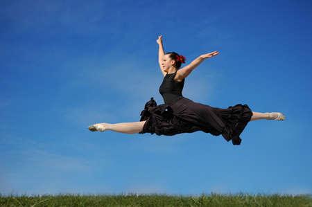 Dancer jumpimp on grass against a blue sky Stock Photo - 7772629