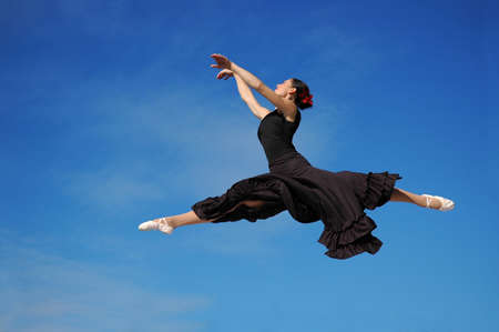 Dancer jumpimp against blue sky wearing black photo