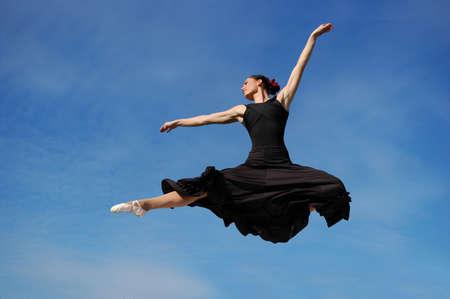 Dancer jumpimp against blue sky wearing black