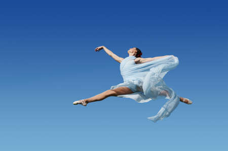 Dancer jumpimp against blue sky wearing blue Stock Photo - 7771578