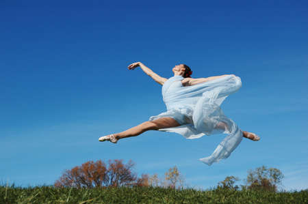 Dancer jumpimp against blue sky wearing blue Stock Photo - 7772834