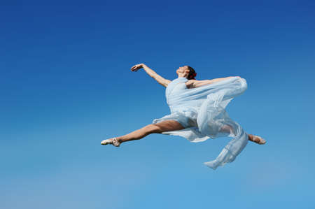 Dancer jumpimp against blue sky wearing blue photo
