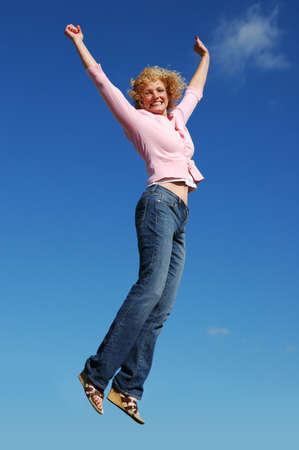 jumpinp girl against a blue sky photo