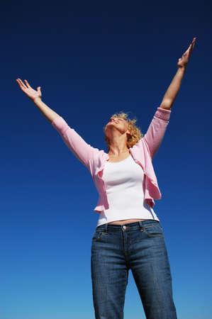 arms wide: Donna con le braccia spalancate nel culto contro un cielo blu