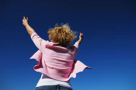 Woman with her arms wide open in worship against a blue sky photo