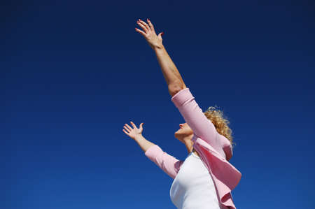 arms wide open: Woman with her arms wide open in worship against a blue sky Stock Photo