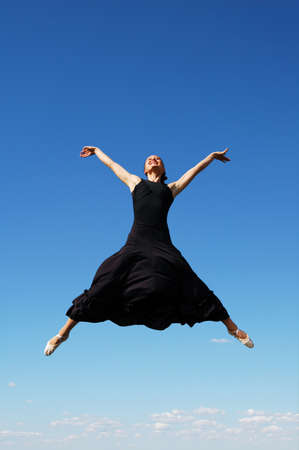 ballerina jumping high against a blue sky Stock Photo - 7774144