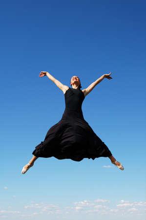 ballerina jumping high against a blue sky Stock Photo - 7774144