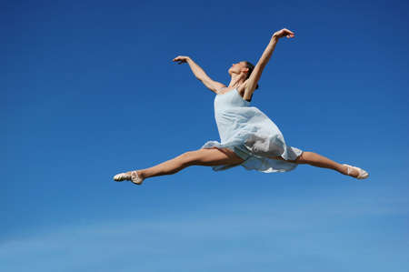 woman freedom: Ballerina performing a jump on a sunny day Stock Photo