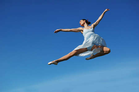 teen dance: Ballerina performing a jump on a sunny day Stock Photo