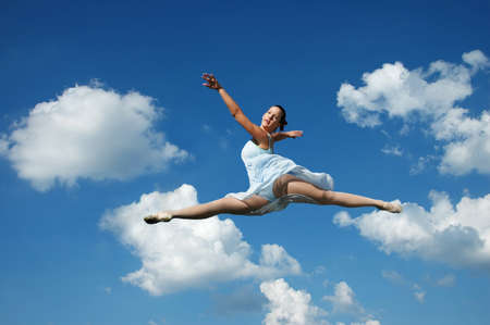 Ballerina performing a jump with clouds in the background photo