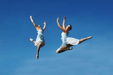 Ballerina's springen tegen een blauwe hemel