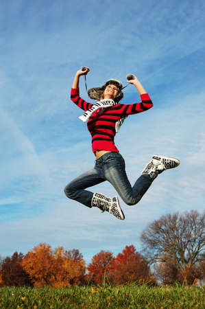 Happy girl jumping of joy on a fall day Banque d'images - 7774212