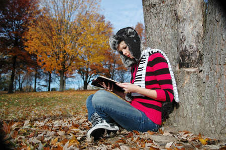 Girl reading the blible on a fall day