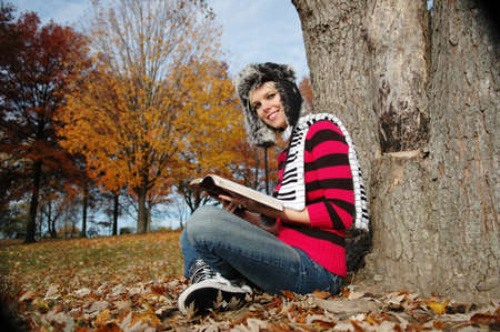Girl reading the blible and smiling on a fall day photo