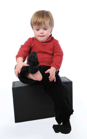 Child with down syndrome puting his socks on isolated on white photo