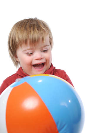 Child with down syndrome p;aying with a ball photo