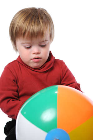 Boy with down syndrome playing with a beach ball Imagens