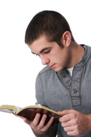 leyendo la biblia: Teen muchacho leyendo la Biblia aislada en blanco  Foto de archivo