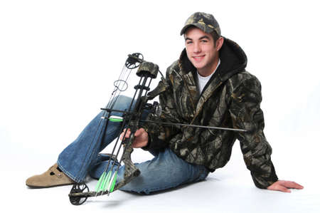 Young hunter with bow and camouflage isolated on white