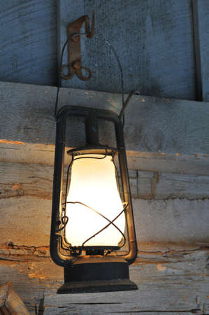 Old vintage lamp hanging from a wooden wall
