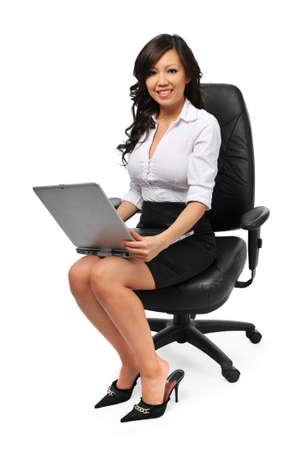 彼女の椅子に腰掛けて、白で隔離されるラップトップ Youns アジア女性実業家