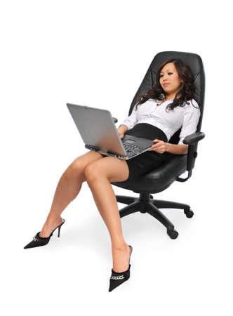 ラップトップを白で隔離されるリラックスと美しい女性実業家