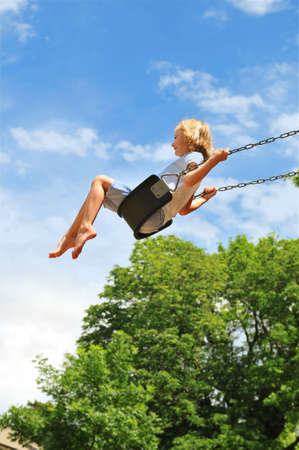 Little girl swinging on a sunny day with trees in the background Stock Photo