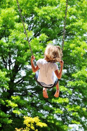 mujer hijos: Ni�a oscilando en un d�a soleado con �rboles en segundo plano  Foto de archivo