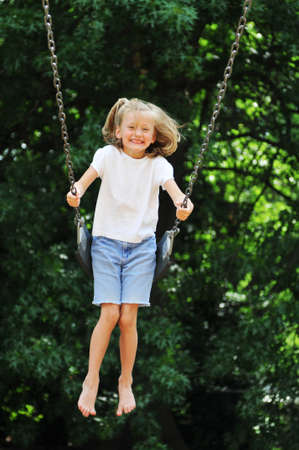 playground ride: Little girl swinging on a sunny day with trees in the background Stock Photo