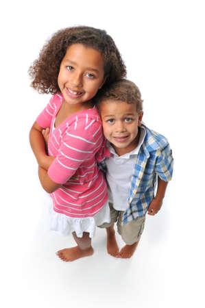 Broer en zus glimlachend geïsoleerd op wit  Stockfoto