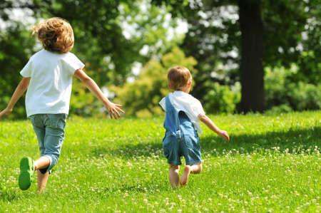 ni�o corriendo: Ni�os que se ejecutan al aire libre en un d�a soleado