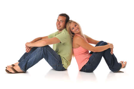 sitted: Young couple smiling and sitted isolated on a white background Stock Photo