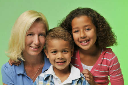 biracial: Mother and childrens portrait isolated on a green background Stock Photo