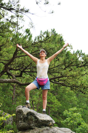 Woman hiker standing on a rock with her arms wide open photo