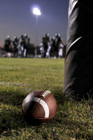 Voet bal op het veld met een lopend spel als achtergrond  Stockfoto
