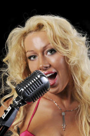 shure: Blond singer on vintage microphone against a black background Stock Photo