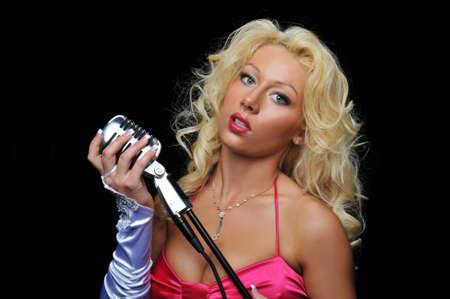 Blond singer on vintage microphone against a black background photo