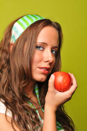 Brunette holding apple against a green background Stock Photo - 7889340