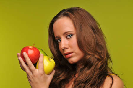 Young woman holding apples isolated agains a green background photo