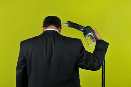 energy crisis: Businessman committing suicide with a gas nuzzle isolated on a green background