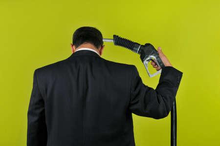 bomba de gasolina: Suicidio de confirmaci�n de empresario con un gas nuzzle aislado en un fondo verde  Foto de archivo