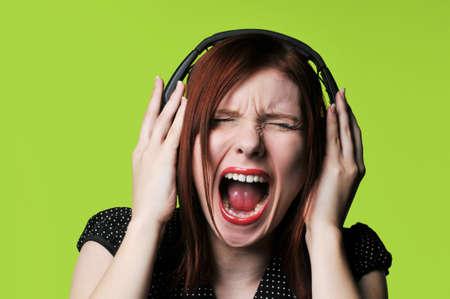 Jonge vrouw met koptelefoon luisteren naar luide muziek tegen een groene achtergrond Stockfoto