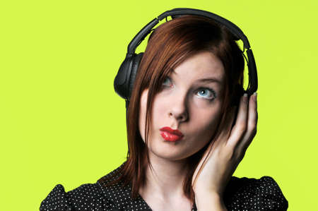 listen to music: Young woman with headphones listening to loud music against a green background