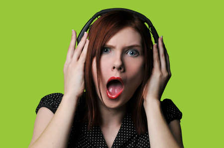 loud: Young woman listening to loud music against a green background Stock Photo