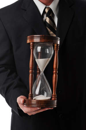 sand timer: Businessman holding a sand timer isolated against a white background Stock Photo